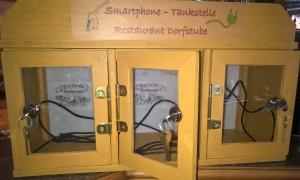 Ladestation Restaurant Dorfstube Holzgau mit drei Ladestationen für mobile Endgeräte.