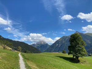Wandern im grünen Gras entlang dem Lechweg bei Holzgau.